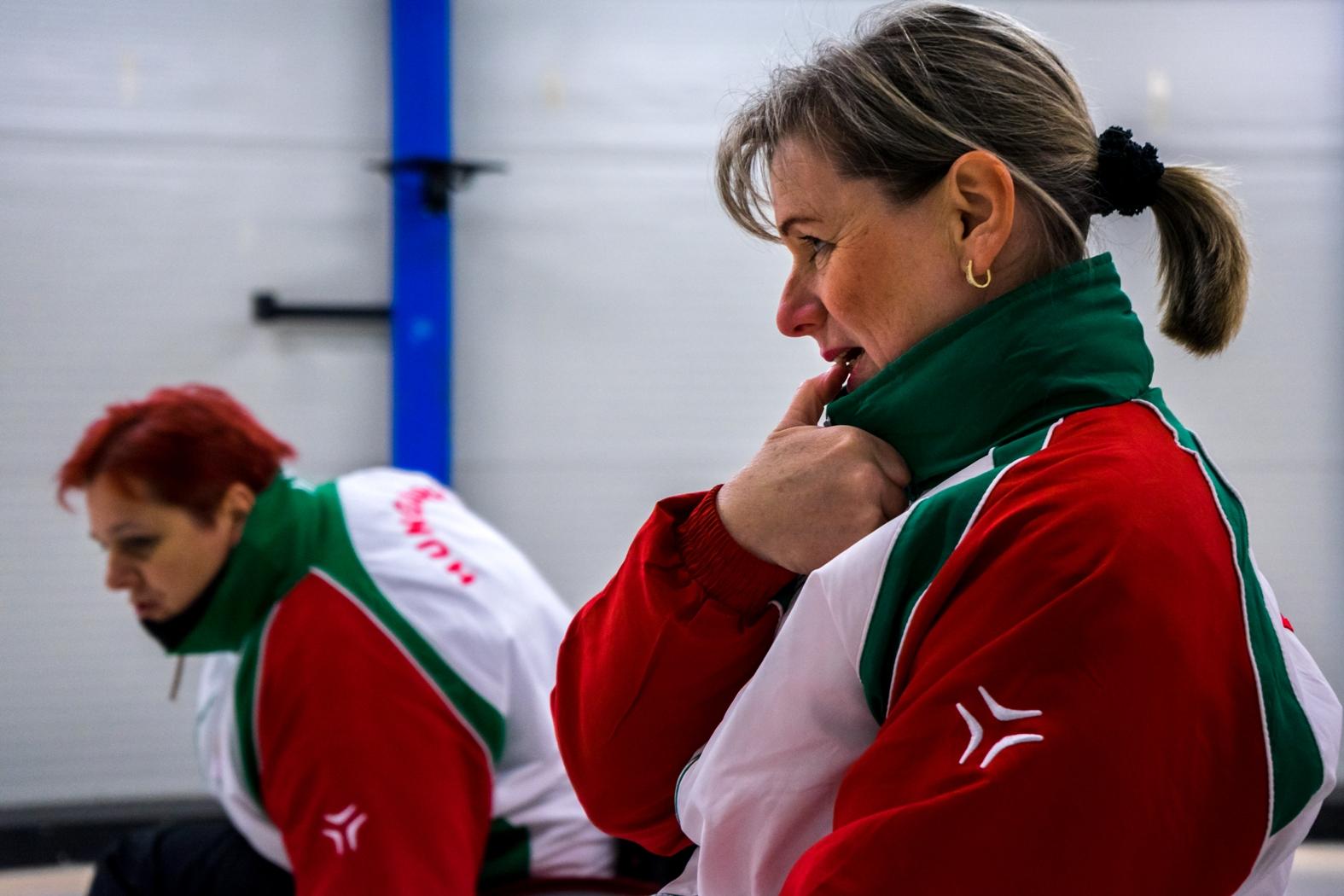 Rita, a magyar válogatott tagja összpontosít a curling kő csúsztatása előtt